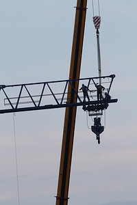 Construction workers setting up a tower crane int he evening...